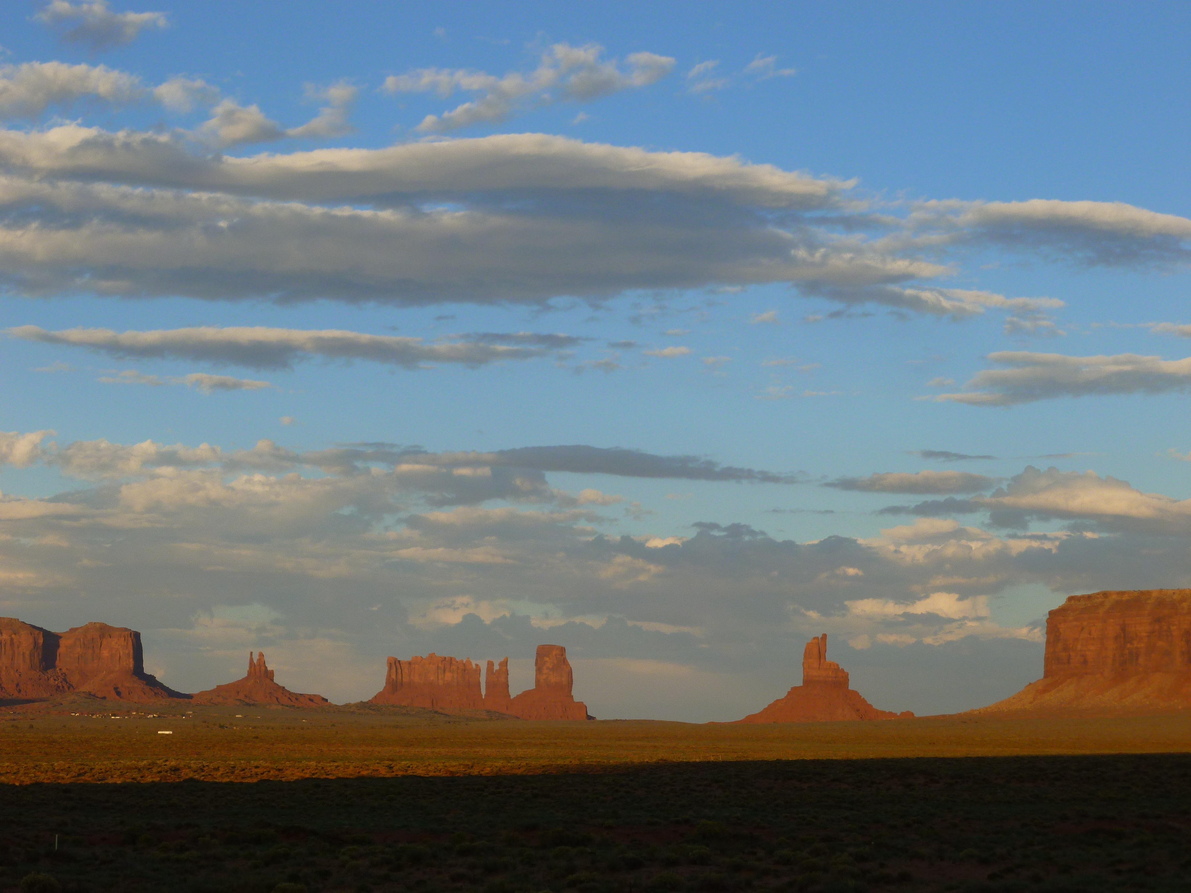 De zon gaat onder tussen de bergen van Monument Valley....