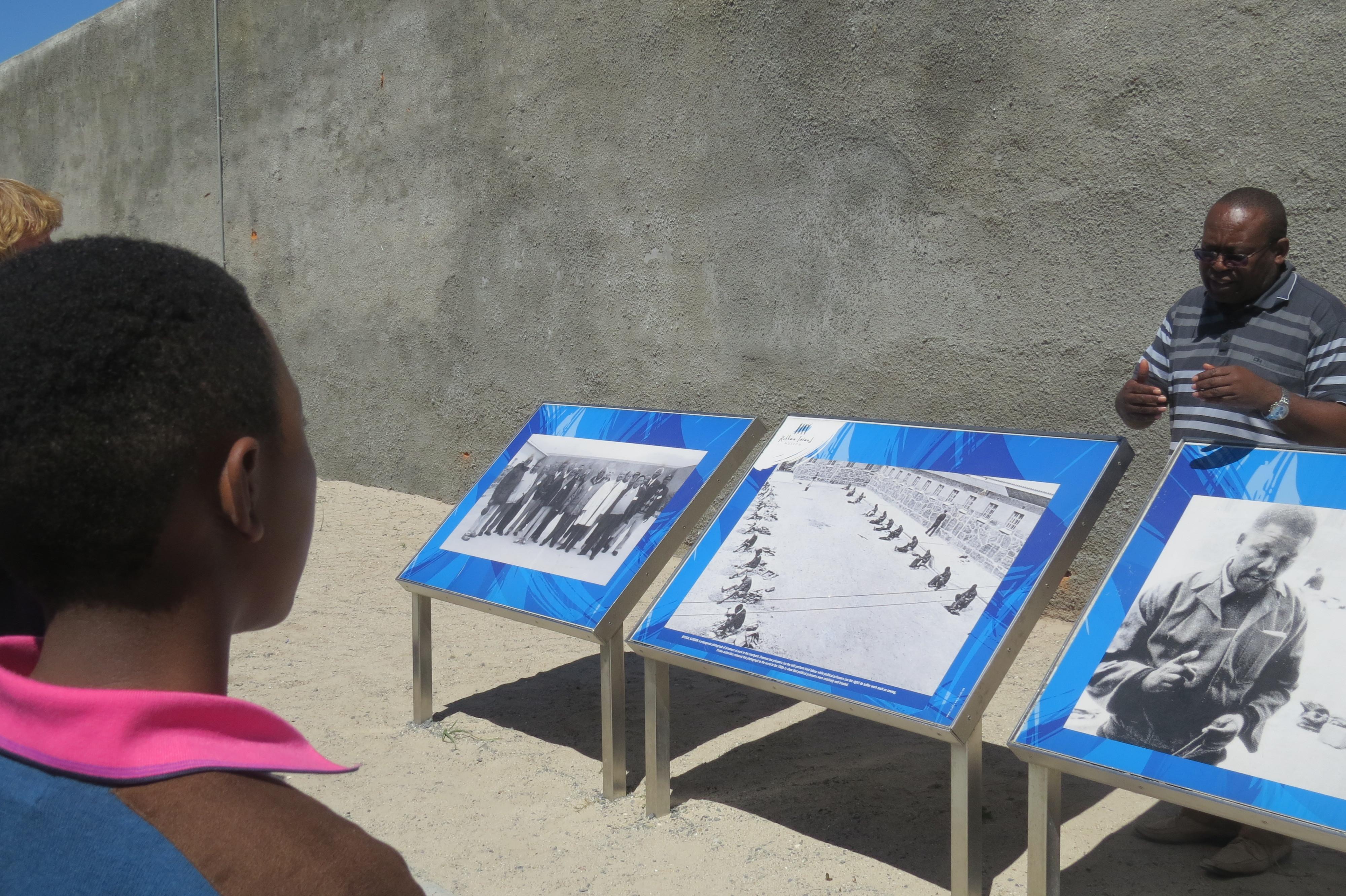 Een afrikaanse jongen luistert aandachtig naar de uitleg van een ex-gevangene