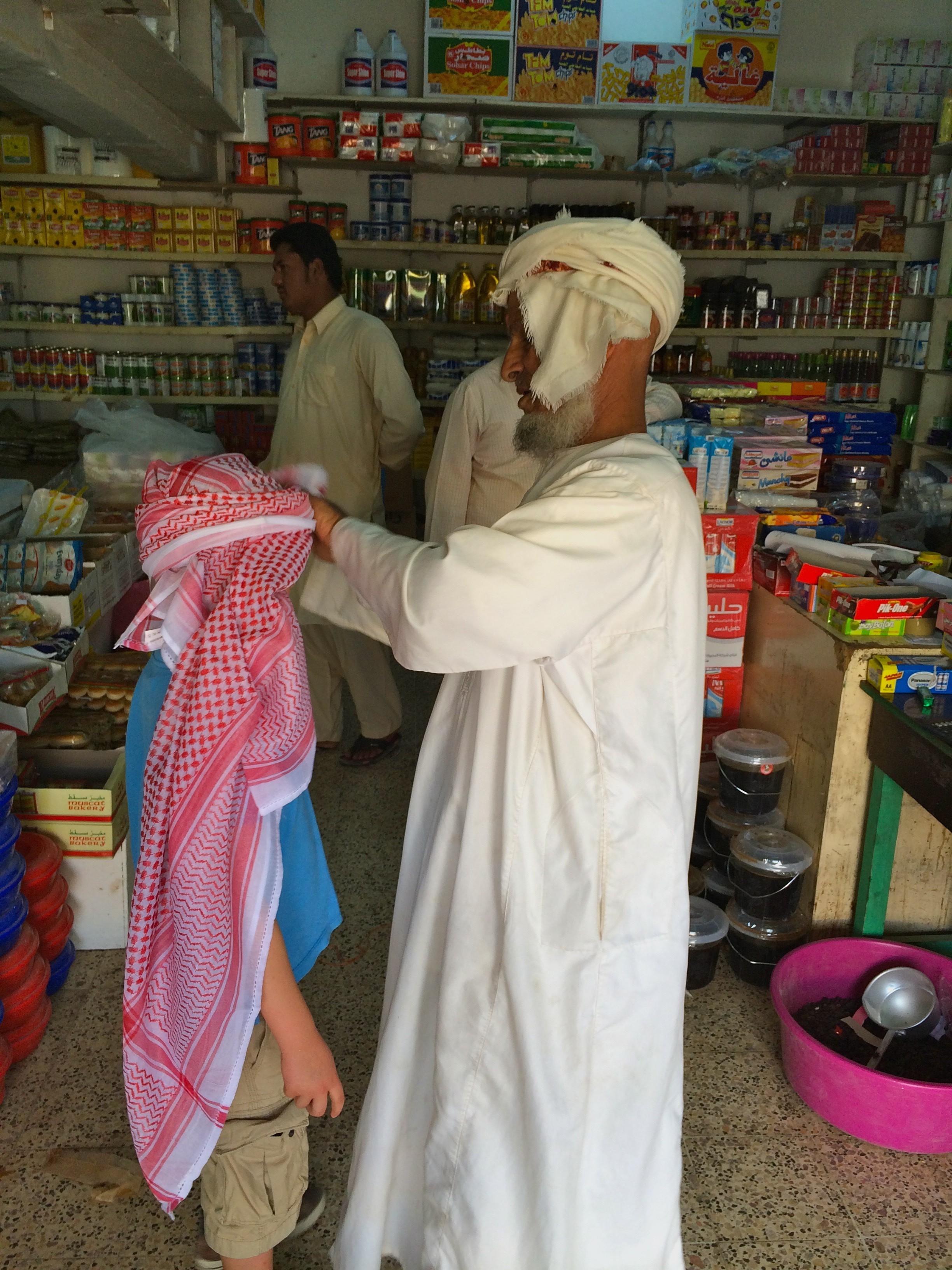 Pepijn krijgt een keffiyeh ter bescherming tegen het zand en de zon in de woestijn van Oman