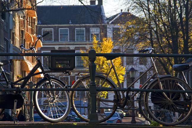 Fietsen op de brug over de bloemgracht, zicht over de Prinsengracht op de Westermarkt en Keizersgracht.